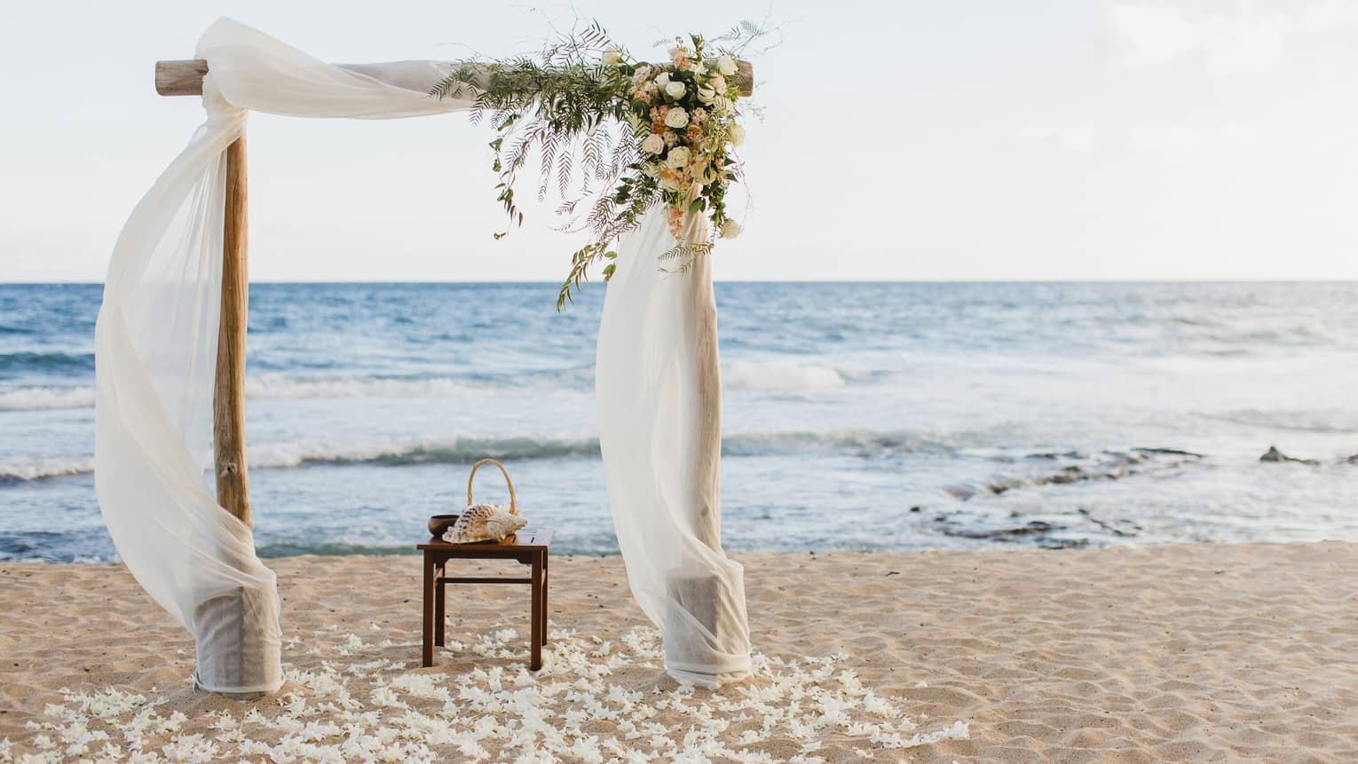 Sand beach wedding altar with flowers, white linens flowing in breeze
