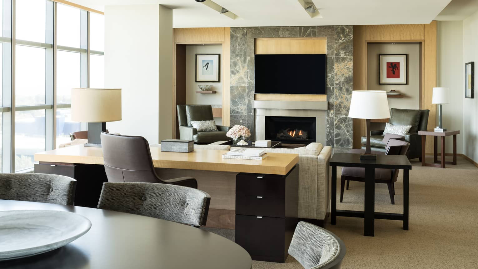 Console table, sofa by modern stone fireplace, TV screen on mantle