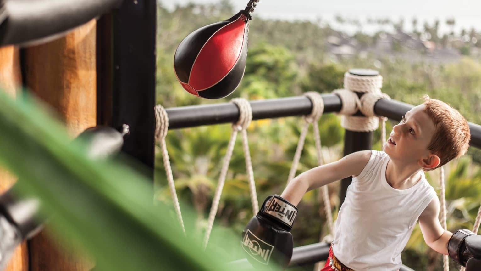 Young boy wearing boxing gloves in ring with small Muay Thai boxing bag