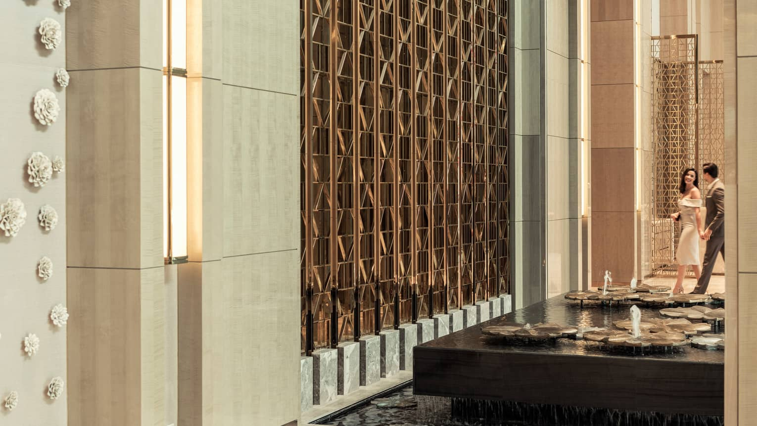 A couple walks through the lobby at Four Seasons Hotel Kuala Lumpur