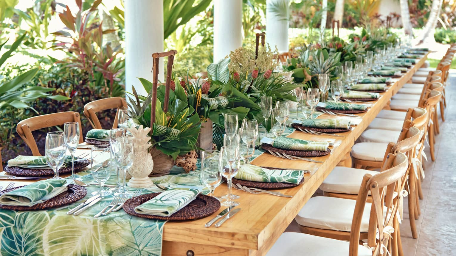 Versailles outdoor terrace with a set table with a green leafy runner and napkins