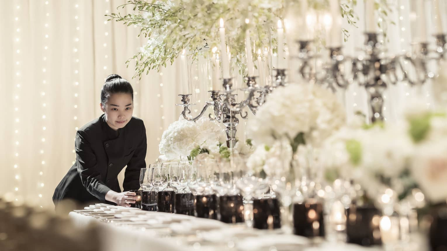 Hotel staff places candle at end of long formal dining table set with candelabras, sparkling lights
