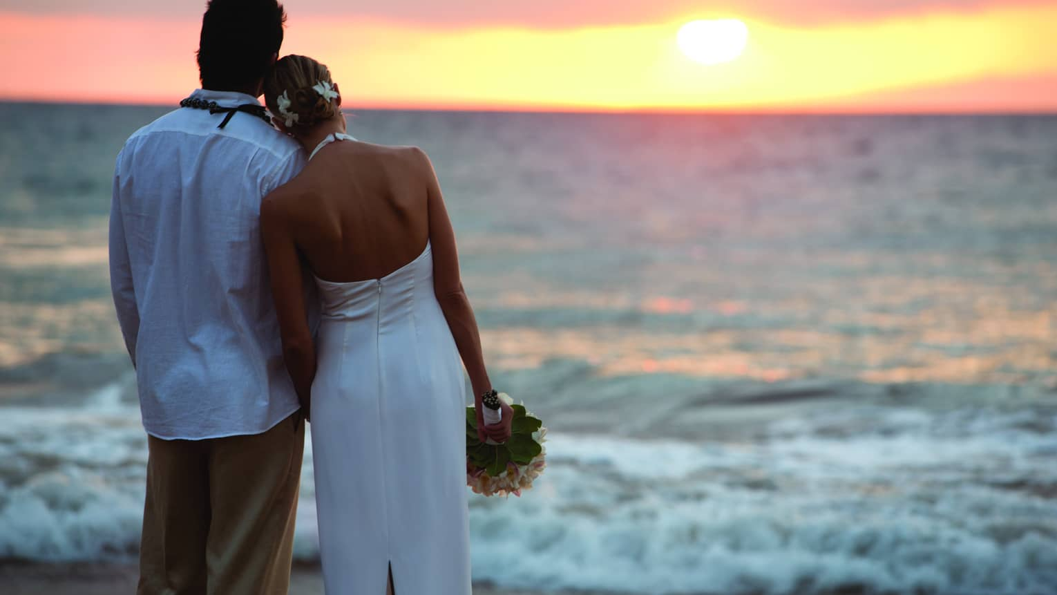 Back of groom and bride in white dress with bouquet look out over beach, sunset
