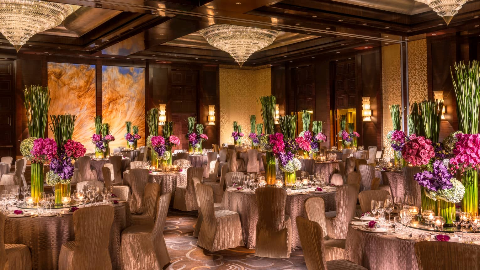 Imperial Ballroom wedding reception with elegant fabric-covered dining chairs, tall floral centrepieces, crystal chandeliers