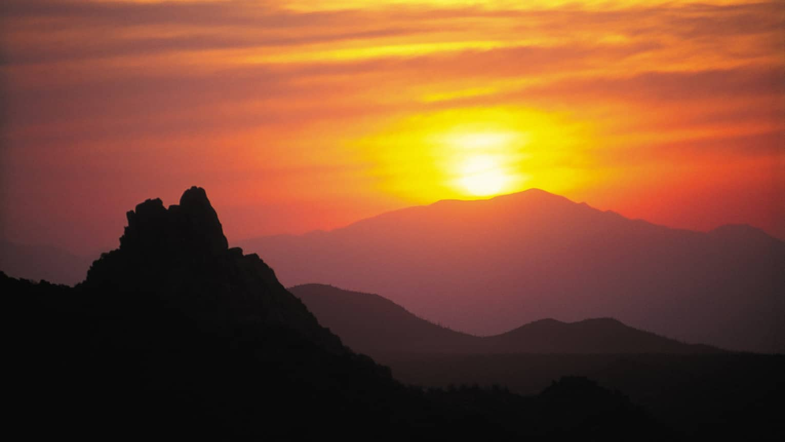 Silhouette of Pinnacle Peak mountain in front of orange sunset