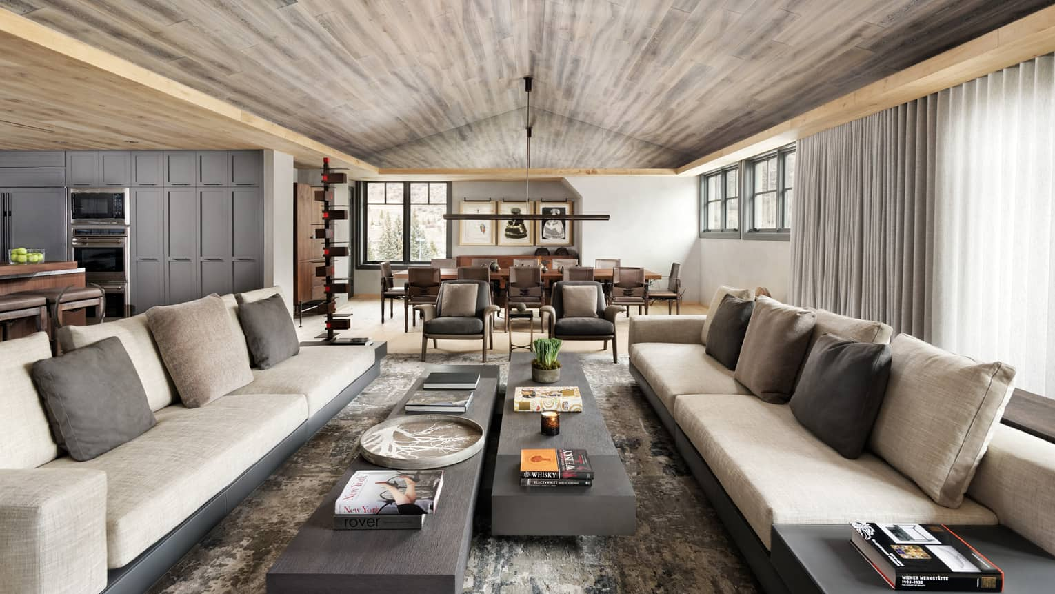 Long beige sofas, two slate coffee tables under wood ceiling