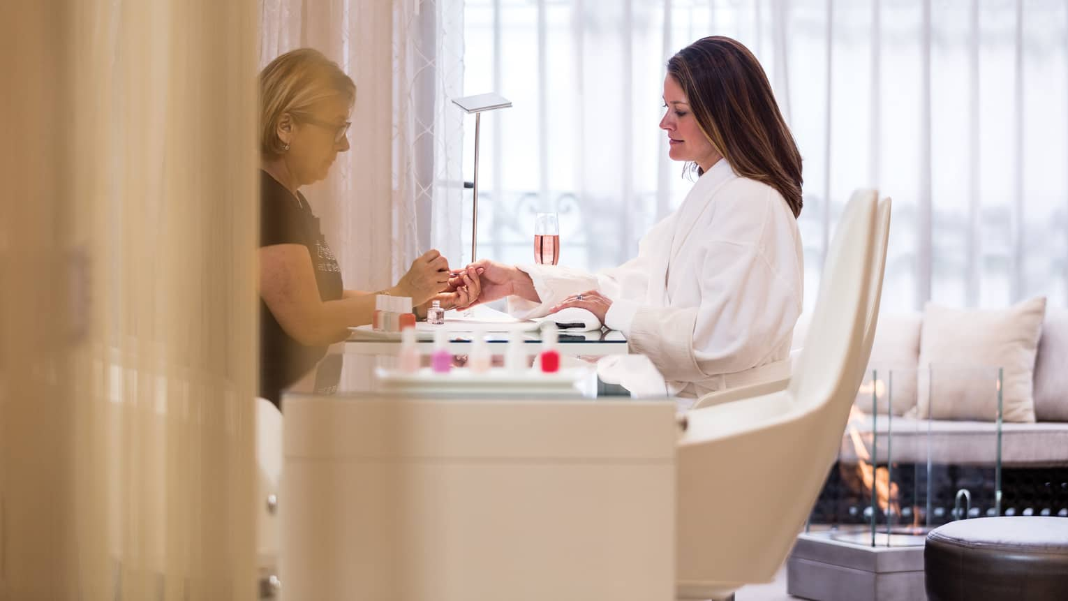 Woman in white robe sits at spa table as salon staff gives her manicure