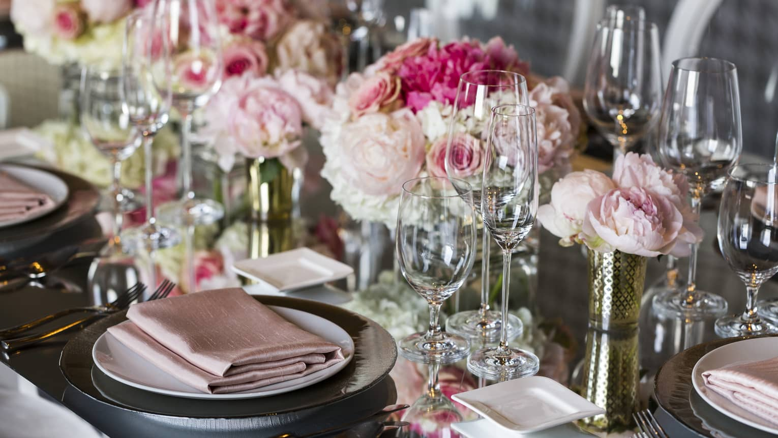 Close-up of wedding table place setting decorated with pink roses, linens