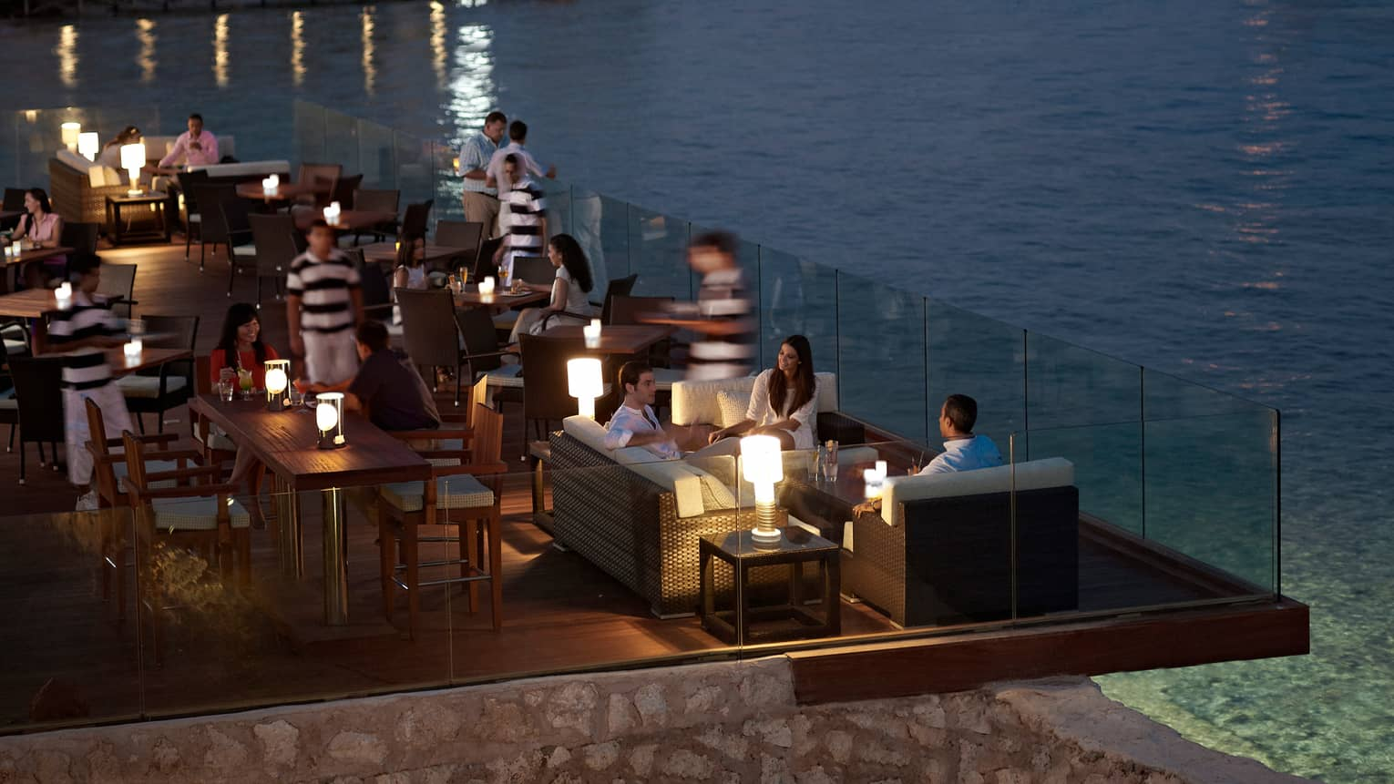 Looking down at guests socializing at tables on Sails Asian Food Lounge patio at night