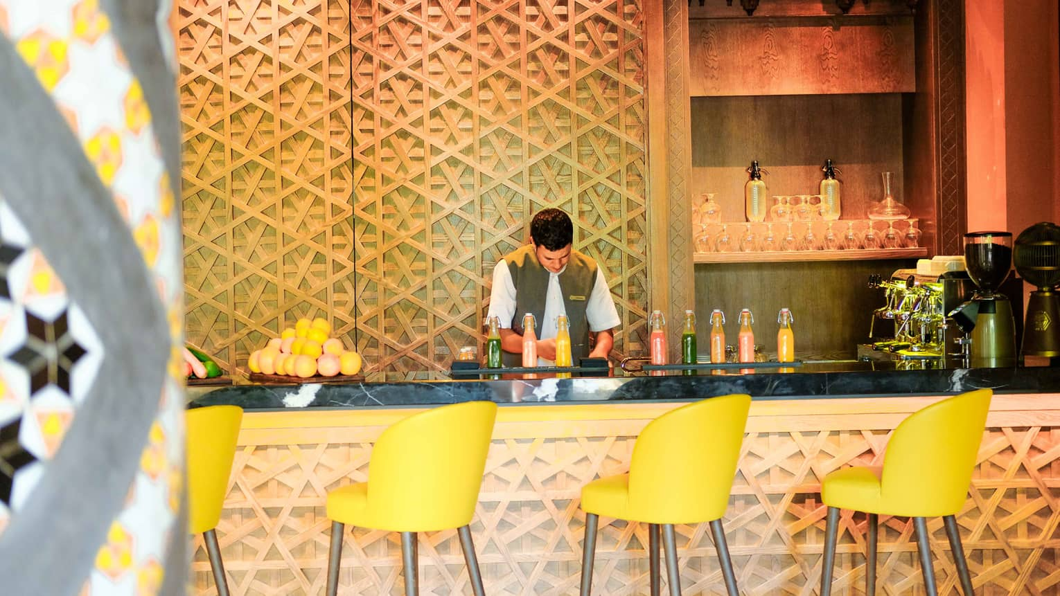 Bartender with fresh juice in glass jugs, fresh oranges on decorative carved bar lined with yellow stools