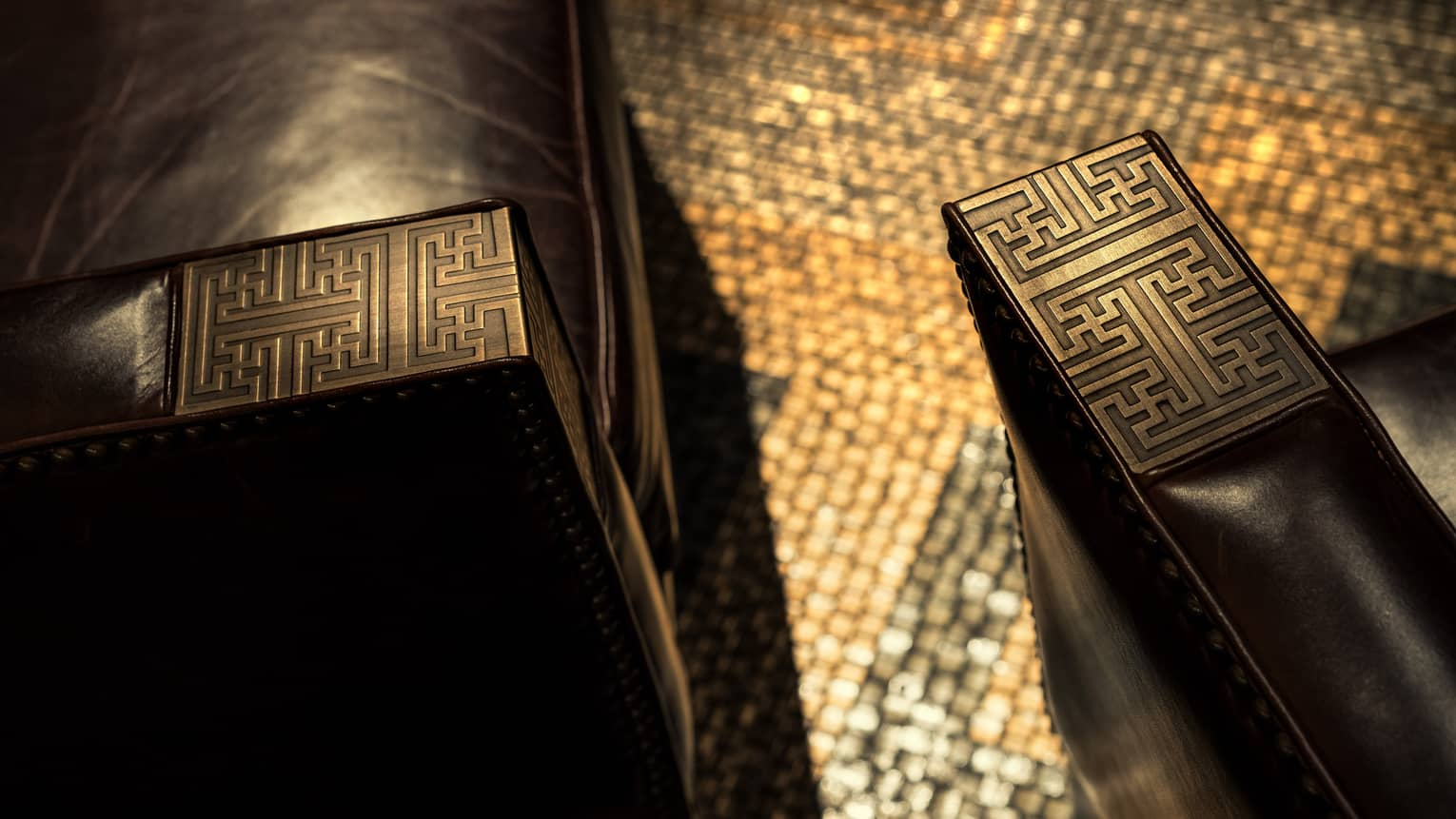 Decorative carved wood details on arms of leather chairs in Charles H lounge