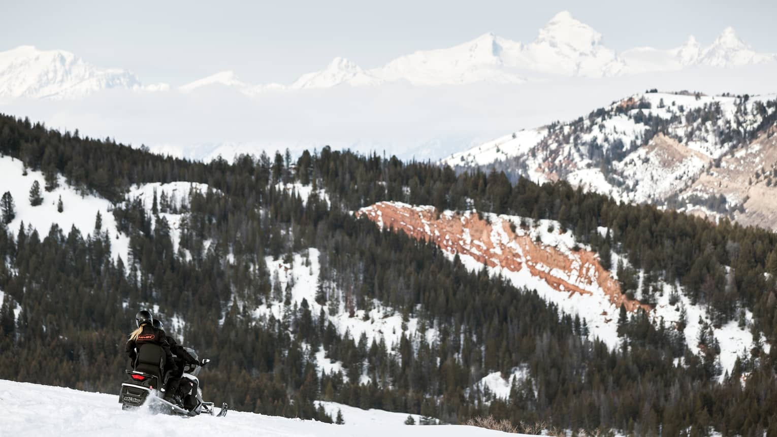 Couple rides snowmobile over mountain slope, trees and mountains in background