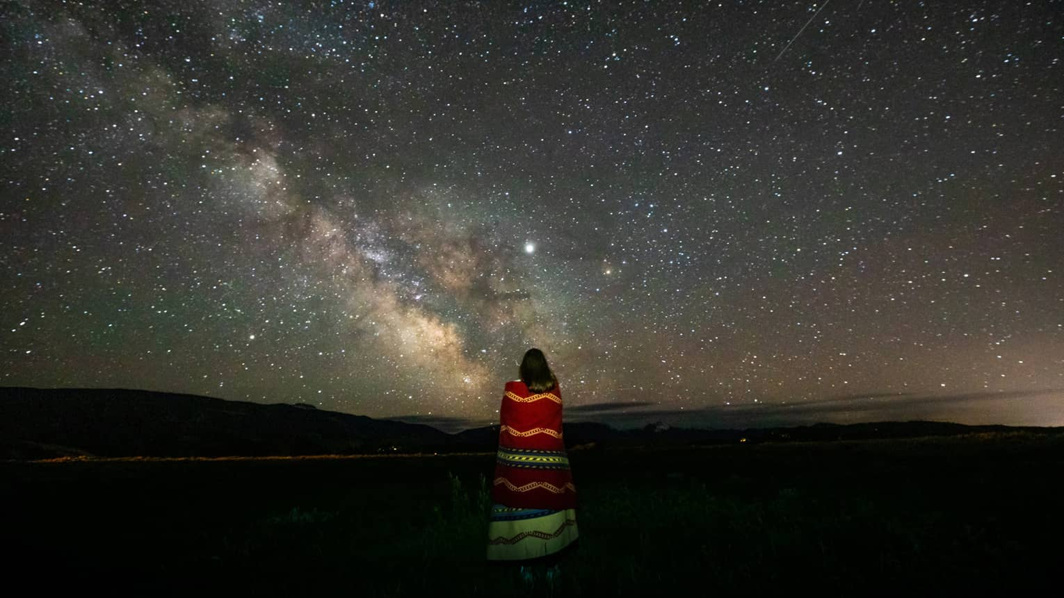 A lone woman stargazes, wrapped in a colourful striped blanket