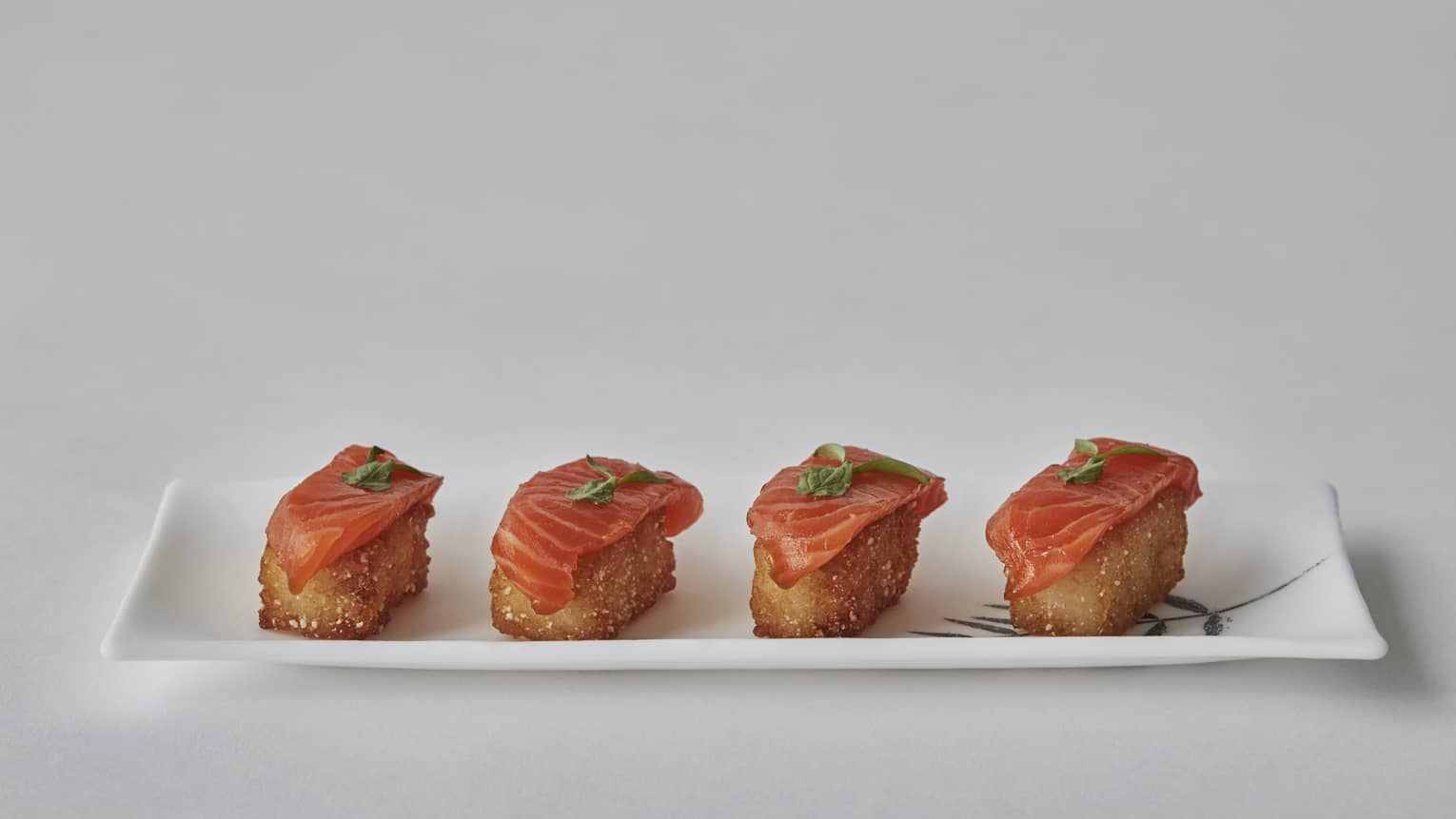 Four salmon bites on a white, rectangular porcelain plate