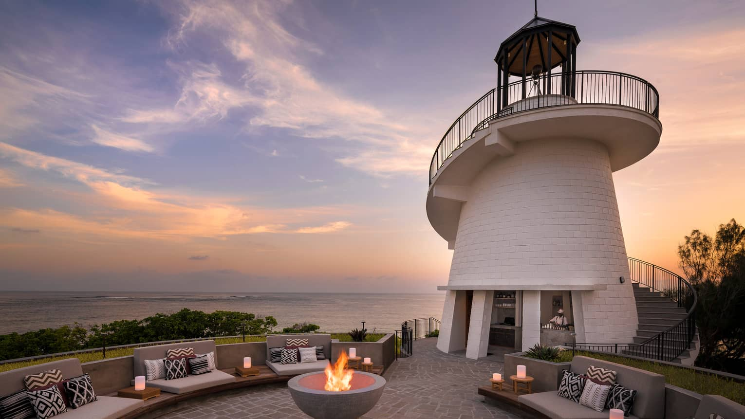 Lighthouse Restaurant illuminated at sunset with fire pit and luminaries