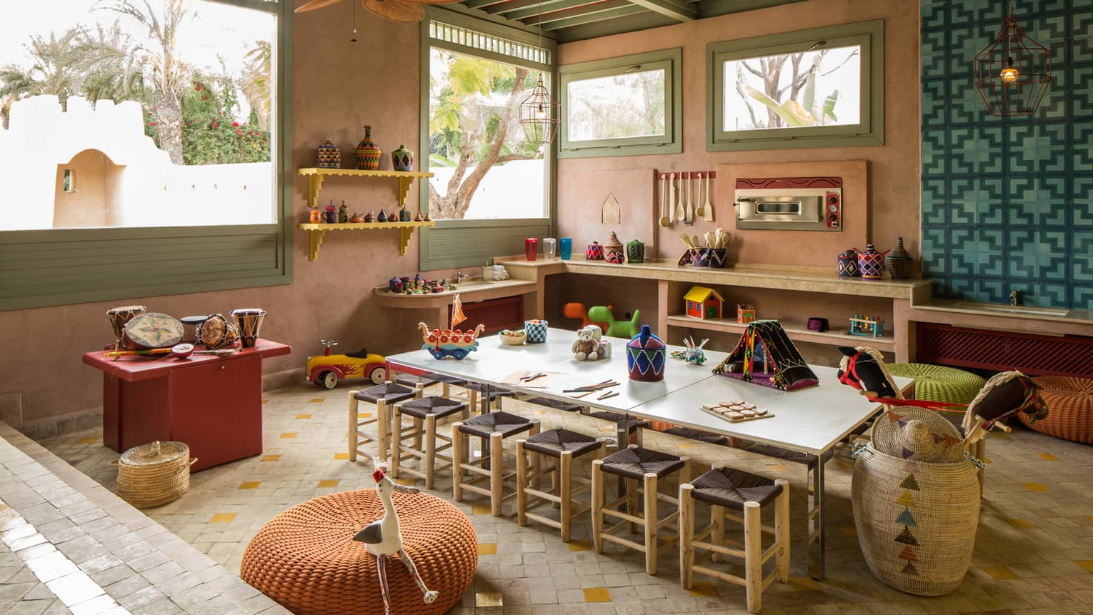 Kids Club long craft table with stools, toys on shelves along wall under sunny windows