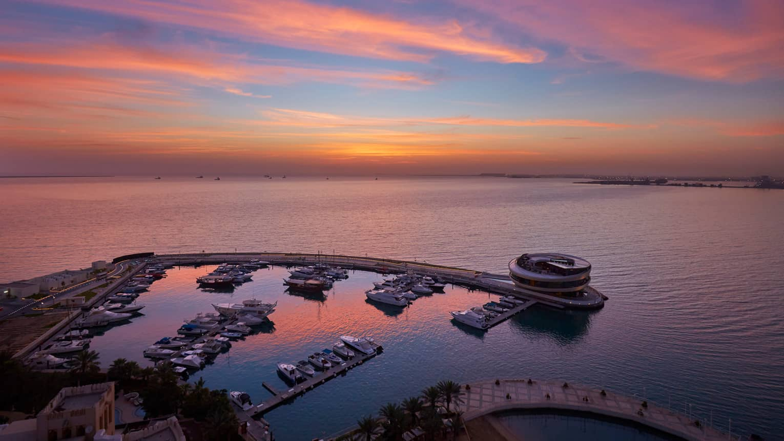 Aerial view of private Four Seasons Marina against the gulf, pink sky at sunset