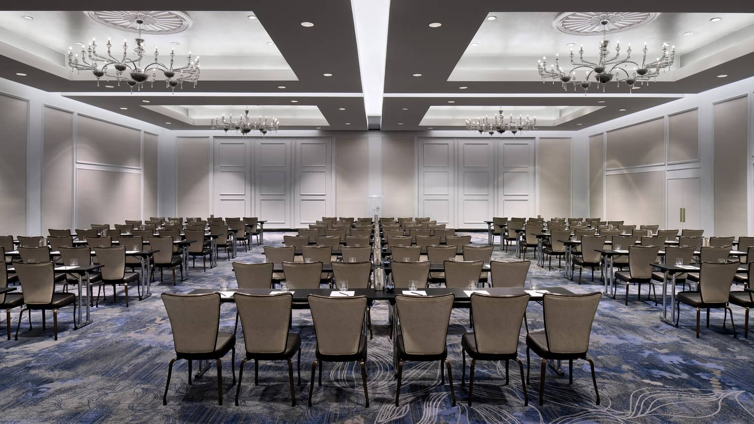 Large ballroom with inset ceilings, recessed lighting, and chandeliers, with several rows of tables and chairs