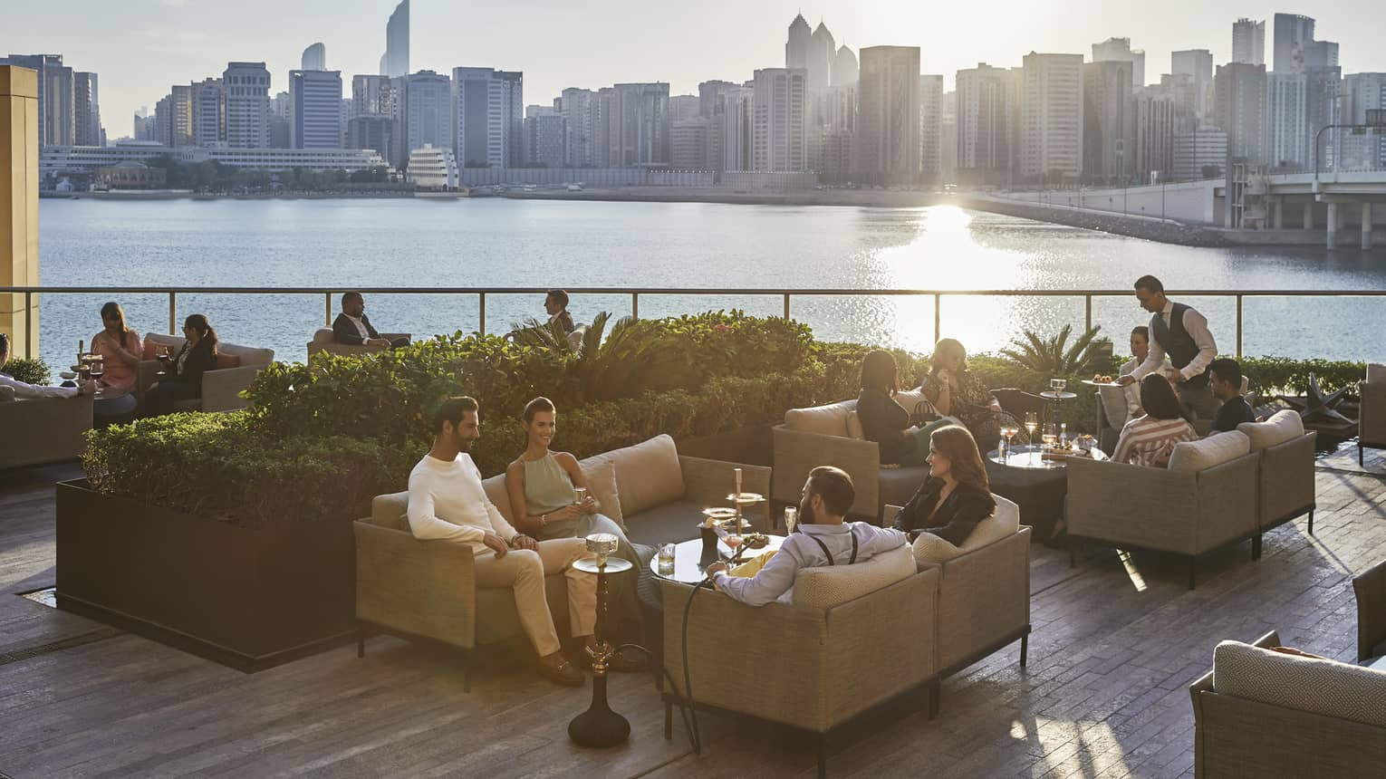 People mingling on sofas of outdoor terrace, overlooking sea and Abu Dhabi city