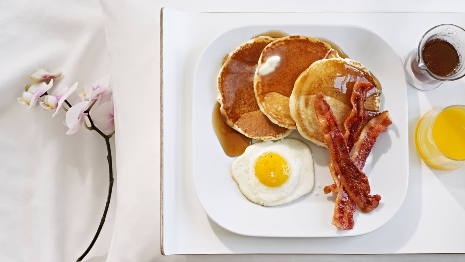 Square white plate with three pancakes, syrup, sunny-side egg, bacon and fresh juice on tray, orchid stem