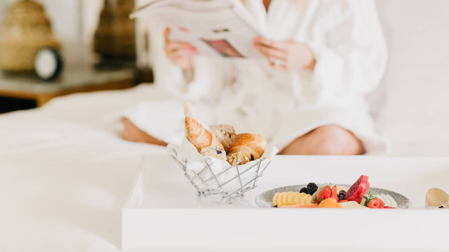 Pastries, fruit on in room dining tray, woman wearing white bath robe reads in background