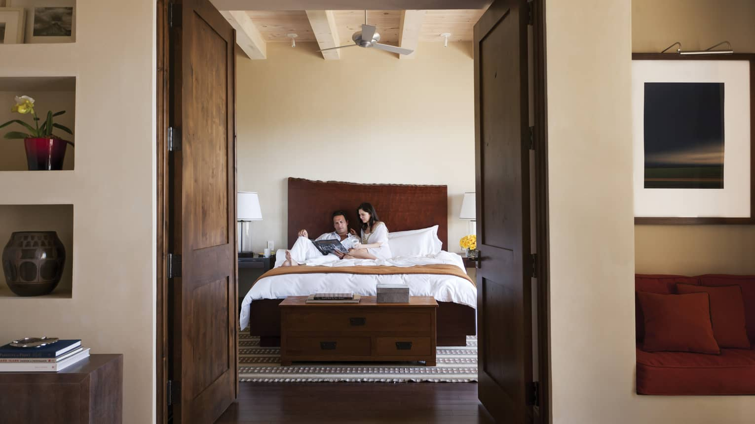 Man, woman read magazine on hotel suite bed past dark wood bedroom doors