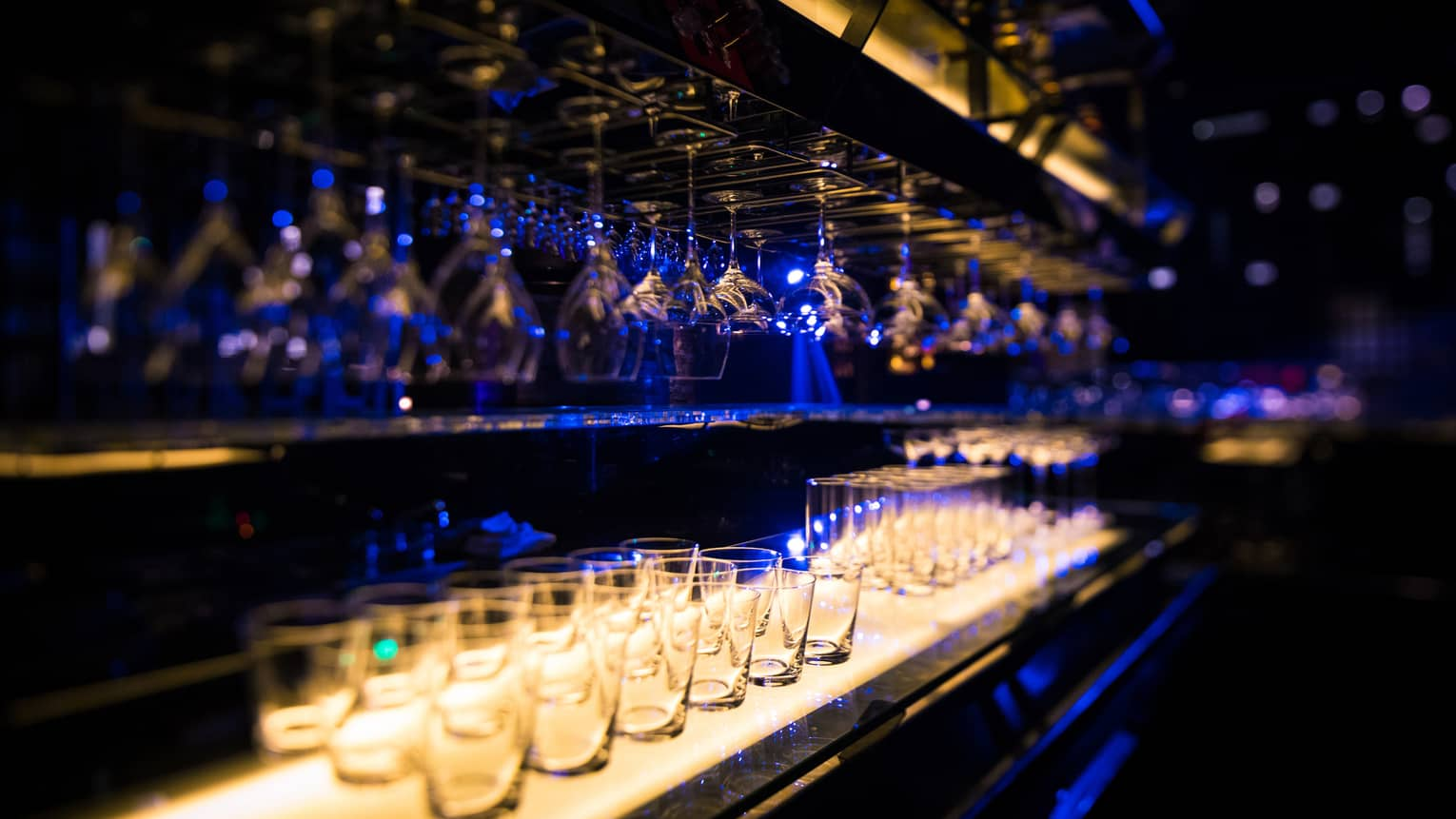 Rows of wine glasses hang over glasses on dark Equis bar with blue lights