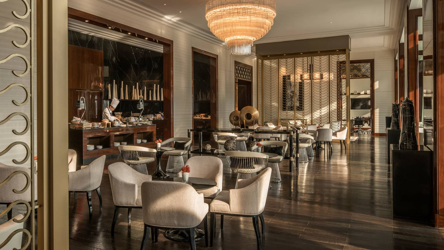 Executive Club lounge chef at bar by cocktail tables, chairs under tiered crystal chandelier