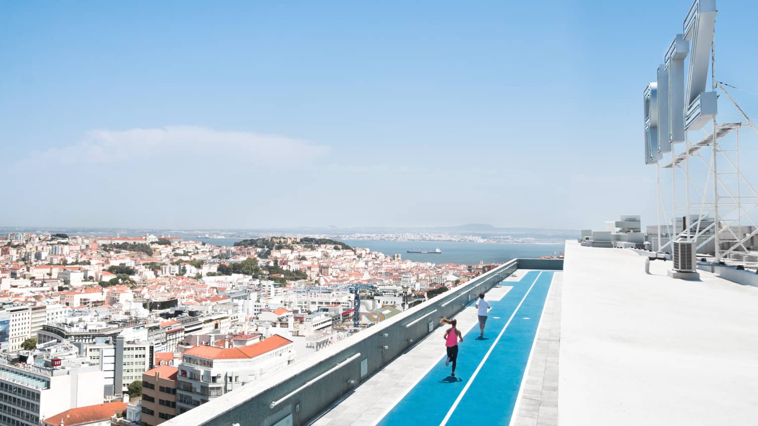 Aerial view of backs of man and woman running on blue rooftop outdoor track, Lisbon city roofs below