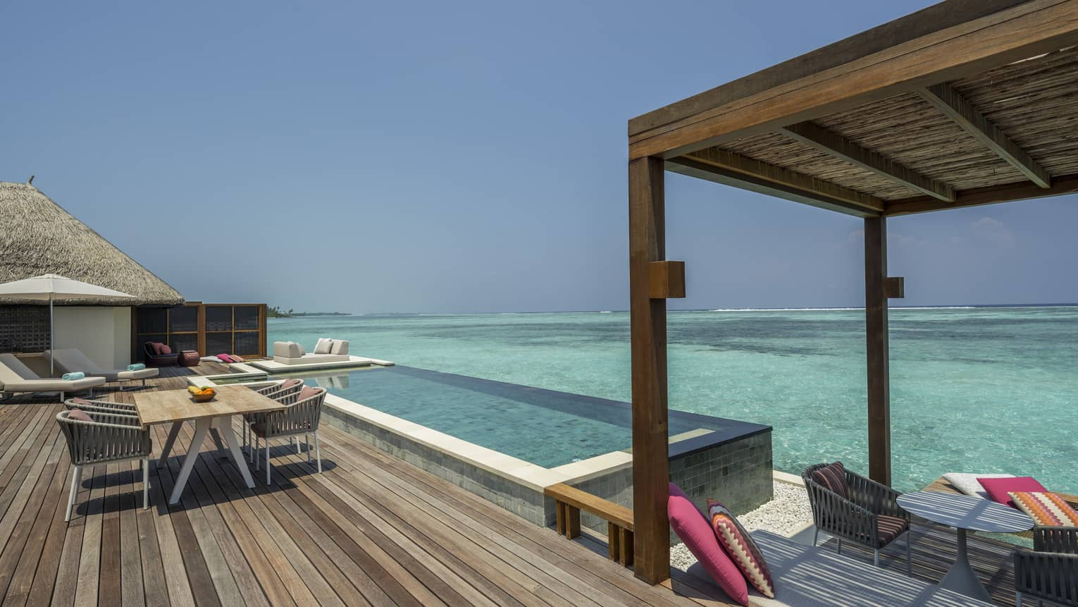 Large wooden deck with dining table and infinity pool overlooking clear turquoise water