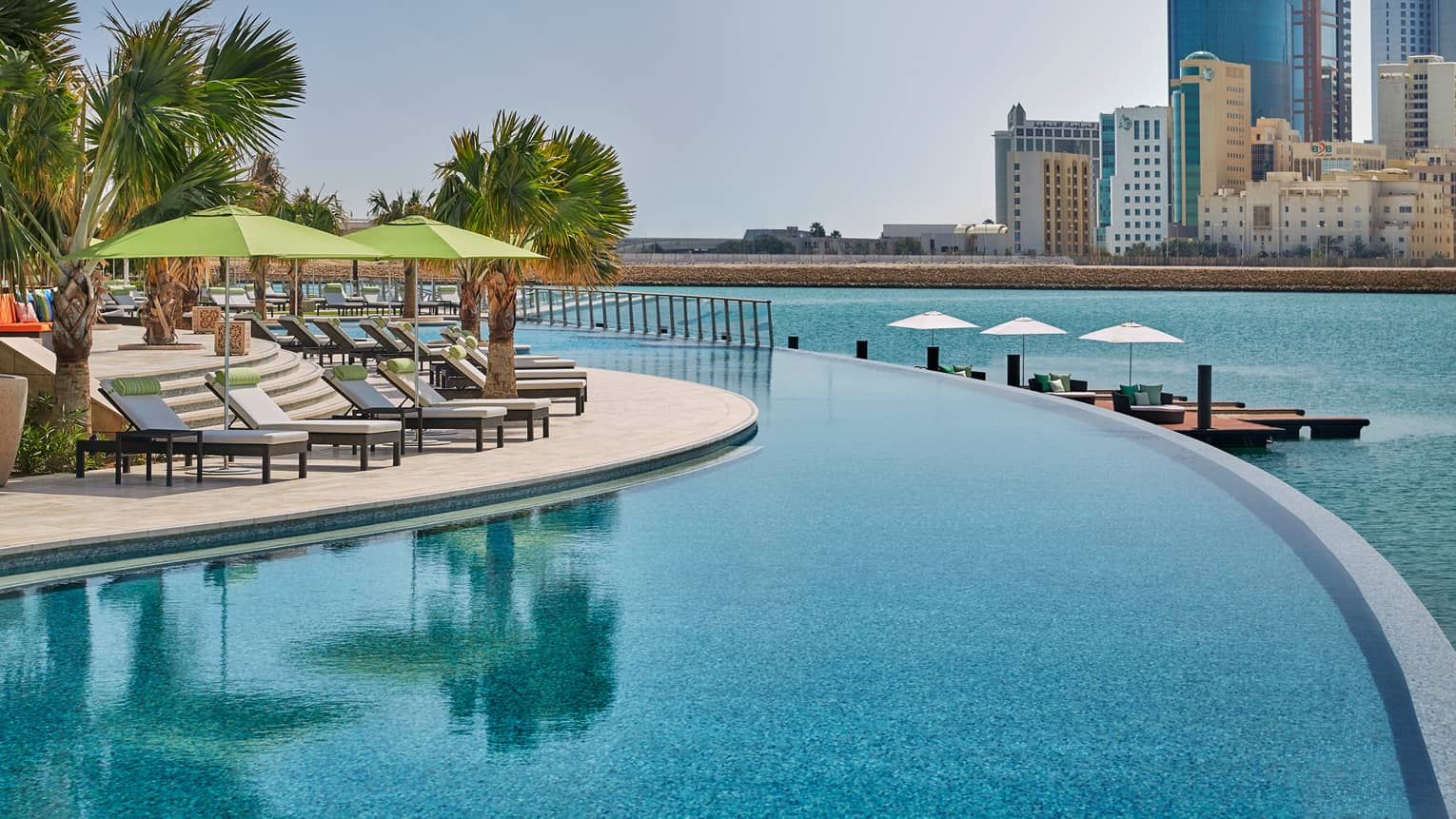 Patio lounge chairs, umbrellas, palm trees line curved outdoor infinity swimming pool along Arabian Gulf