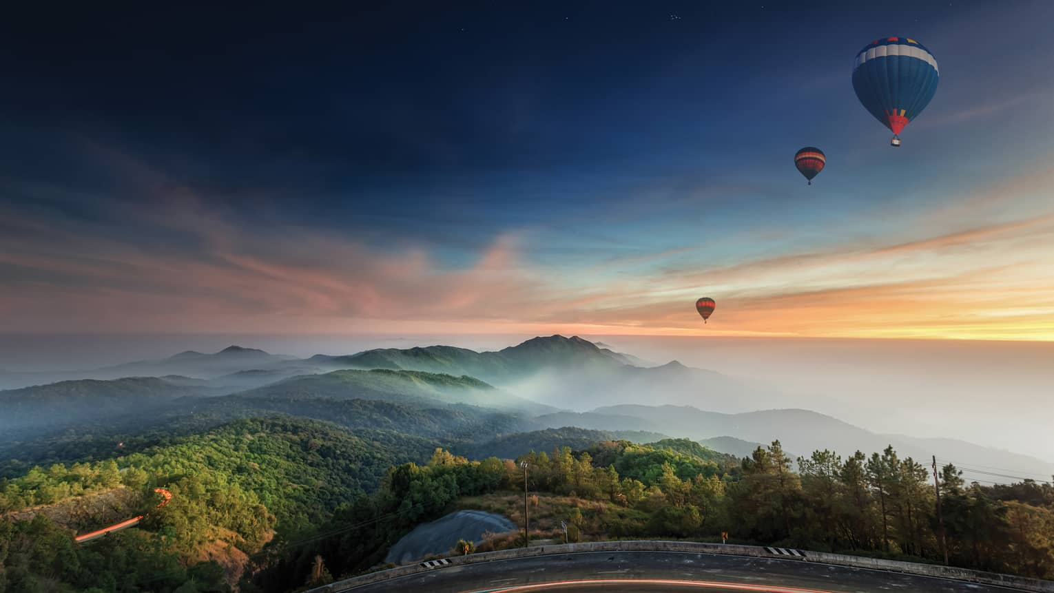 Hot air balloons fly over Chiang Mai at sunrise, mountains in distance