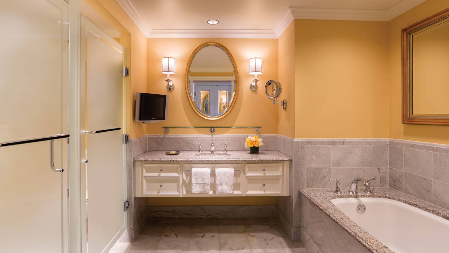 Deluxe Waterfall-View room bathroom yellow walls, flowers on vanity, sink, marble tub
