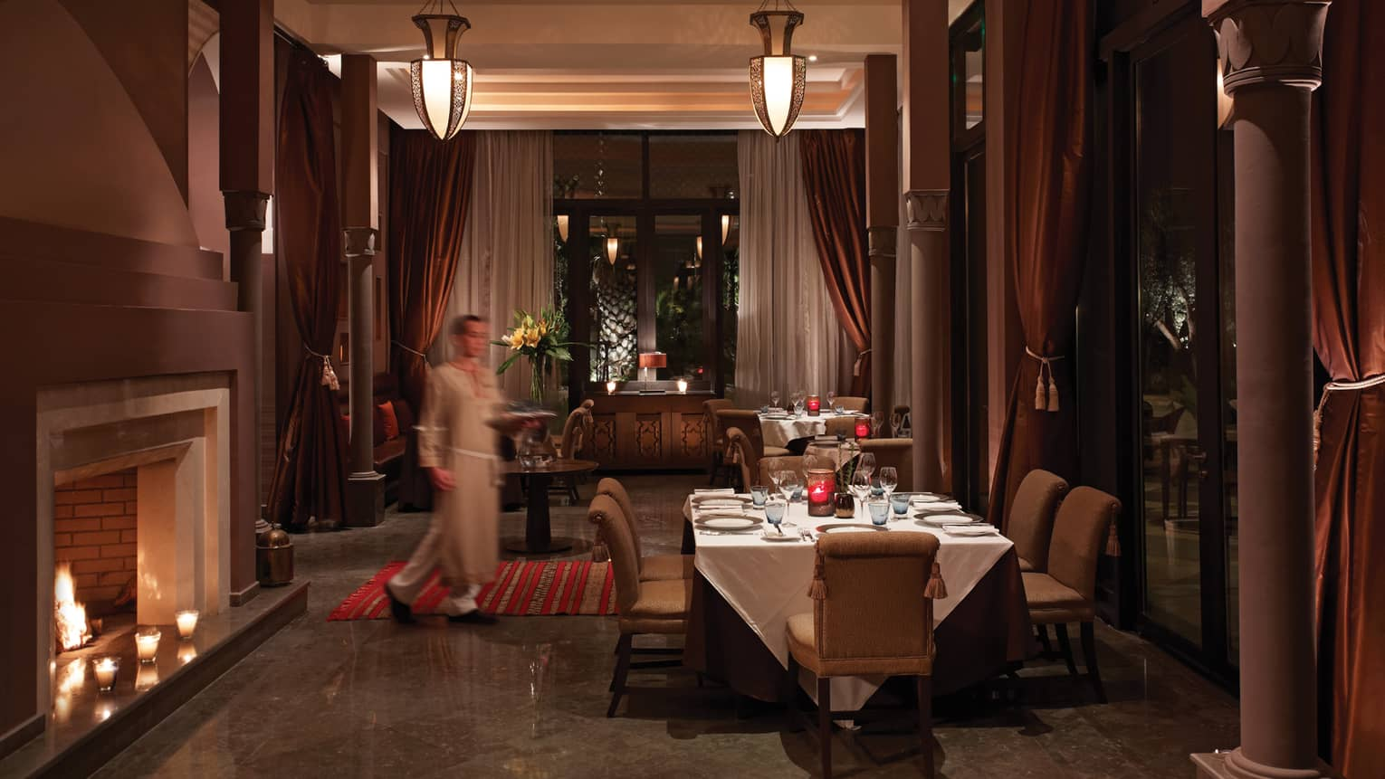 Arancino room, staff carries tray towards private dining table by fireplace