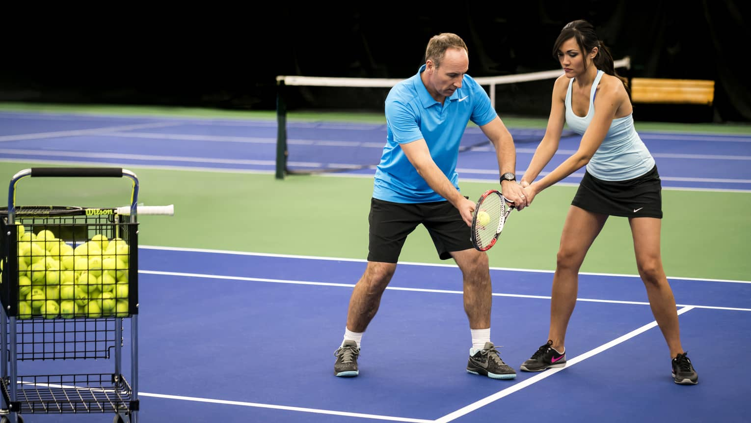 Tennis pro helps woman position racket on blue court near basket with green tennis balls