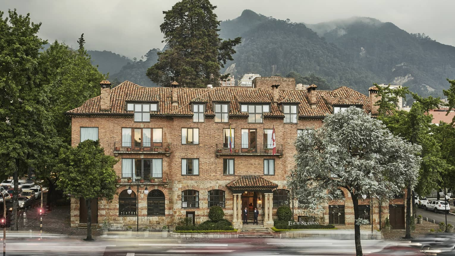 Exterior of historic brick Four Seasons Hotel Bogota, Casa Medina hotel, mountain in background