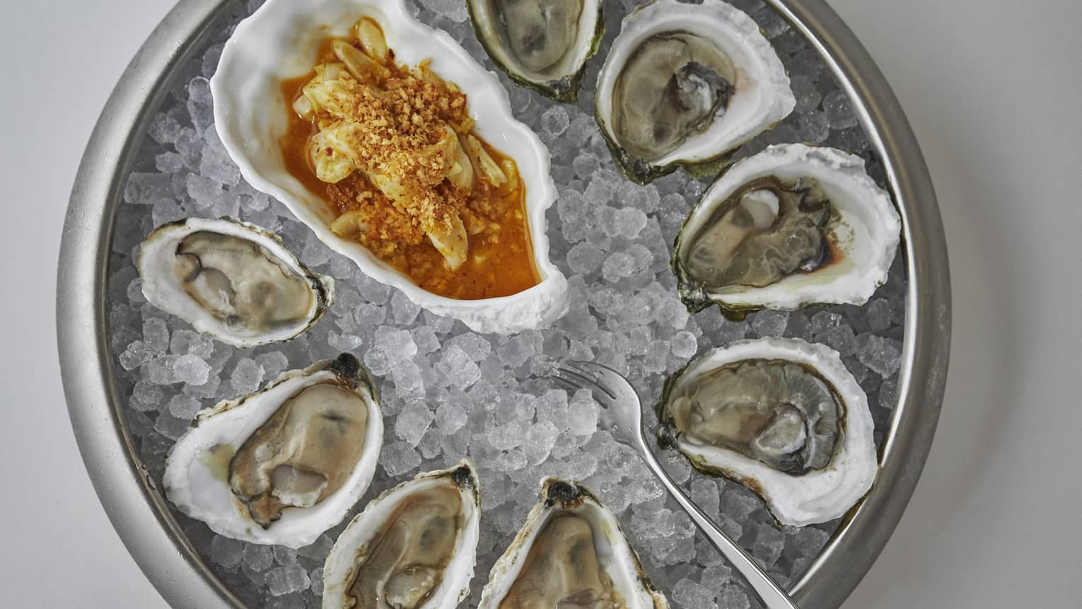 An aerial view of fresh oysters on a plate of ice with a red sauce to the side