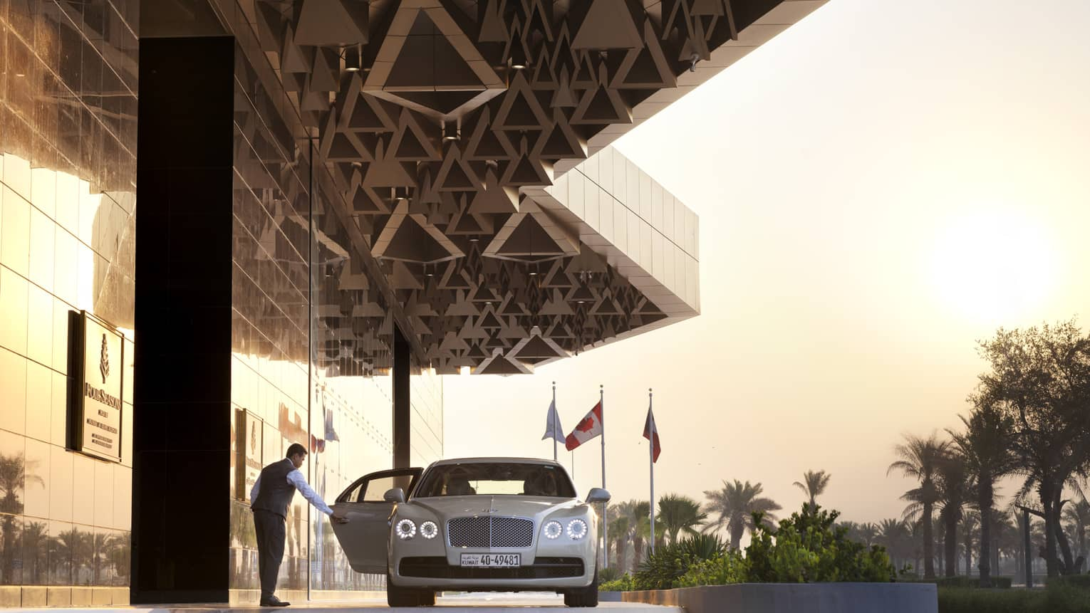 Four Seasons Hotel Kuwait doorman opens luxury car door near entrance
