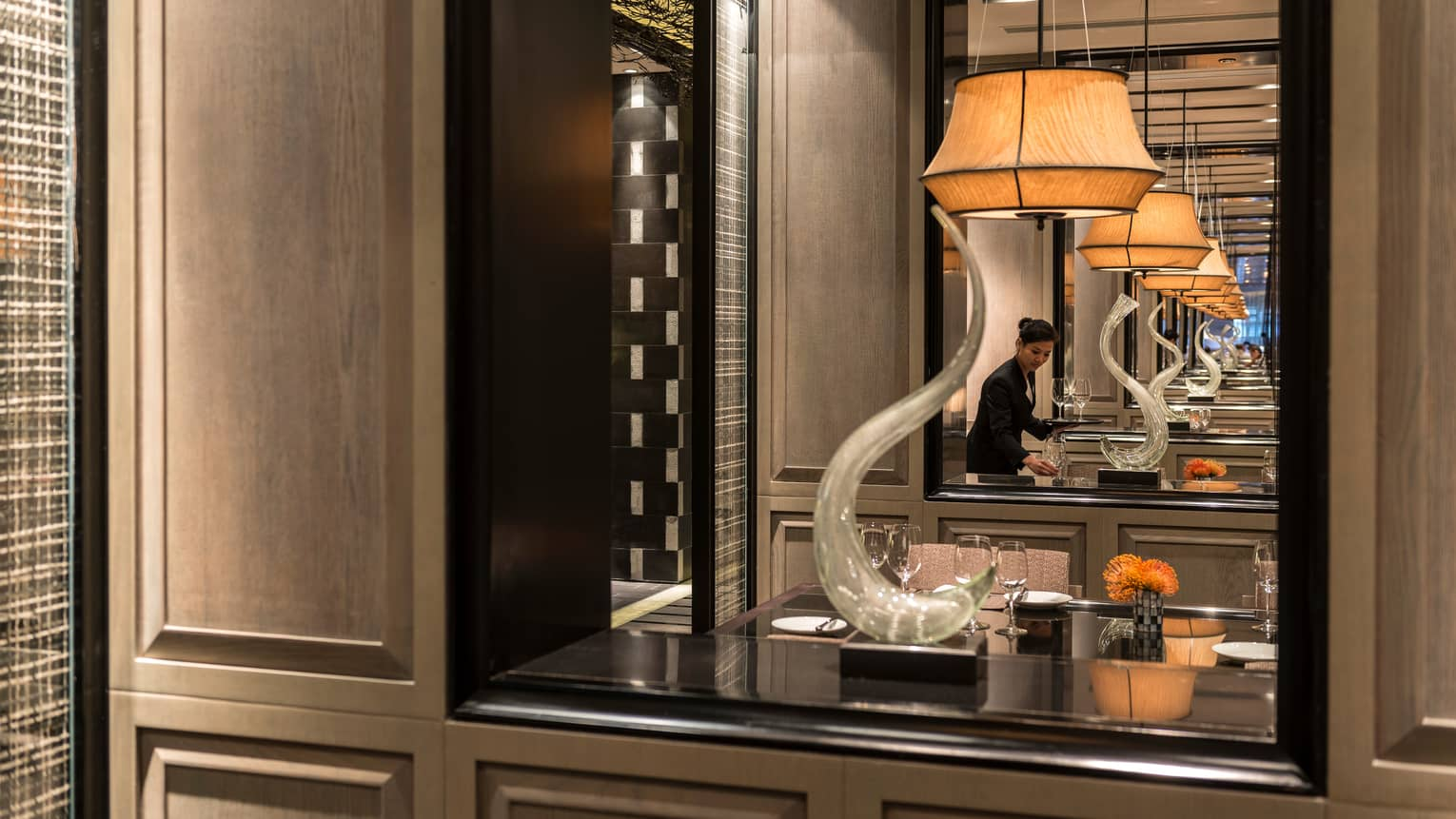 Reflection of Foo restaurant server setting table in mirror by shelf with modern sculpture