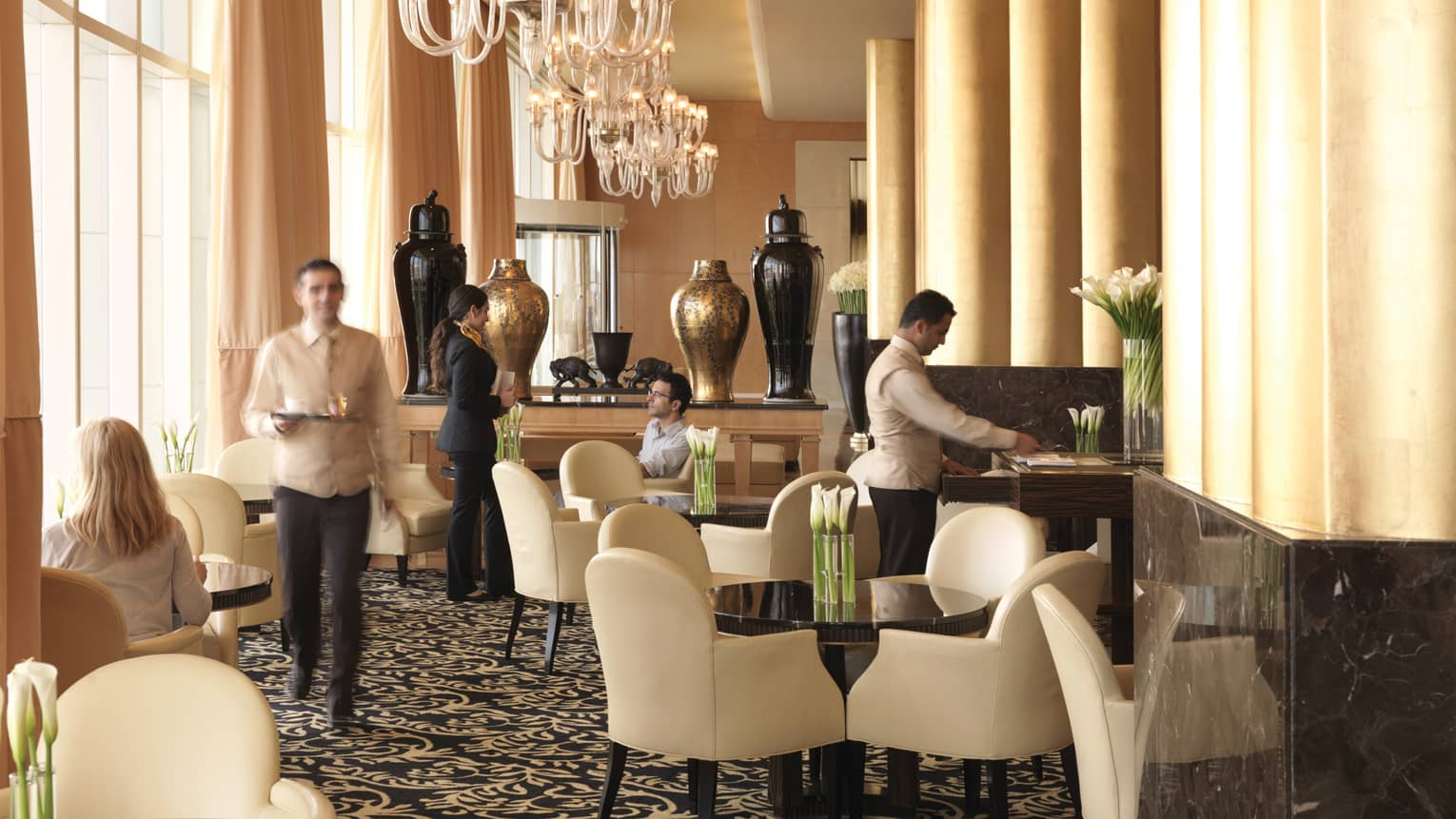 Sunny lobby lounge, hotel staff talk to guests at tables with white leather dining chairs, big gold and black vases behind