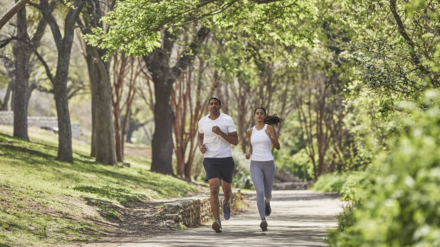 Two guests run together along a tree-lined path