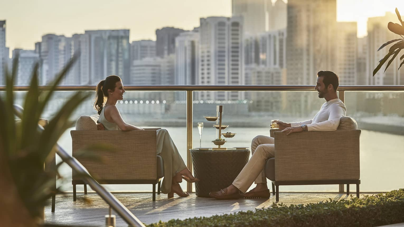 A couple lounges on the Meylas Terrace with wine in hand, as the sun peaks over the skyline, and warms them