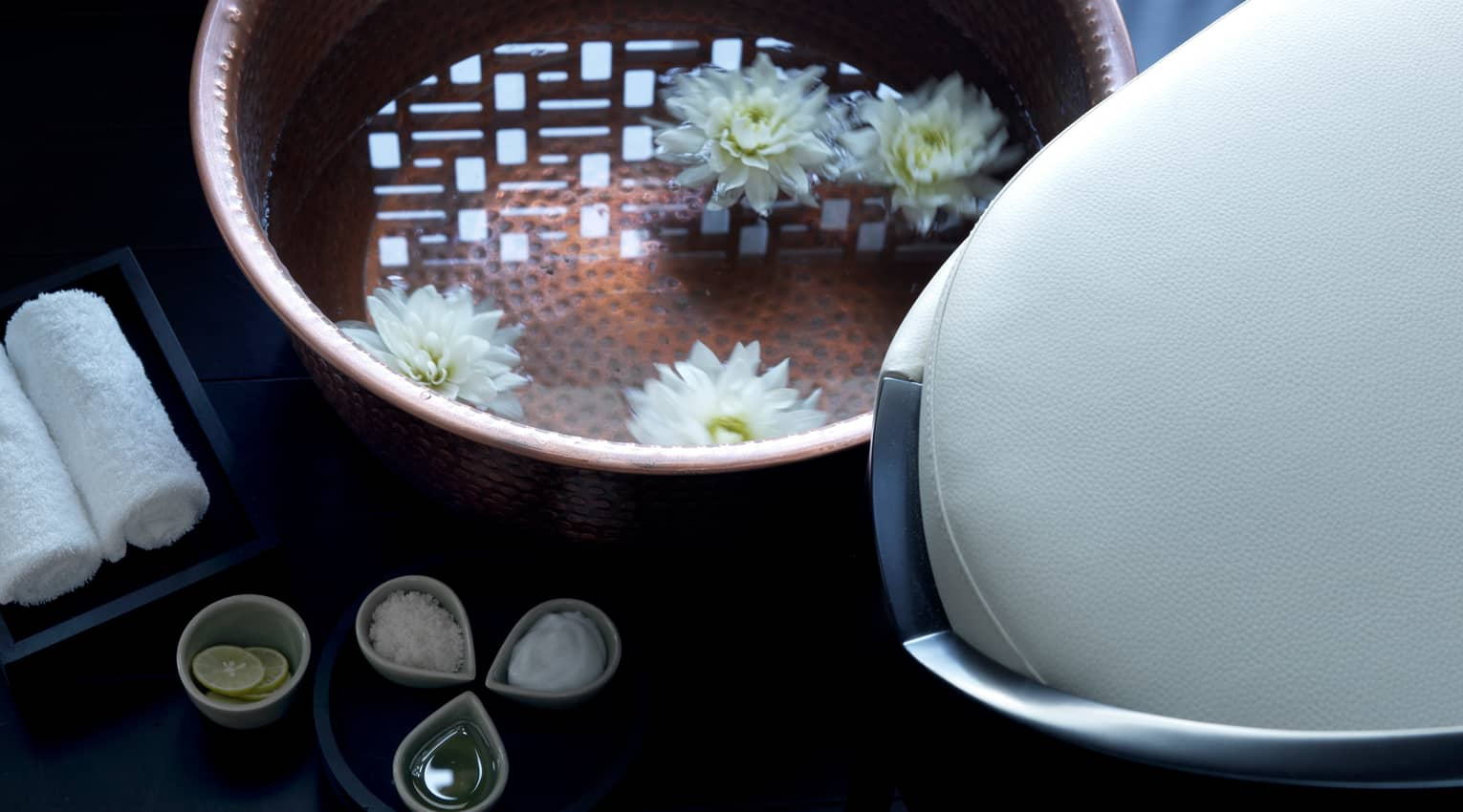 Close-up of copper bowl with water, floating white flowers, small dishes with spa salts, oil and lemons