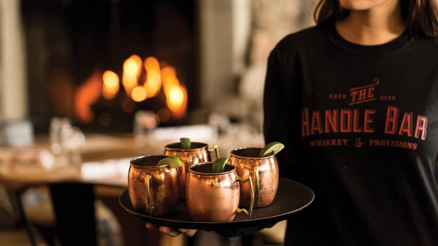 Server with The Handle Bar T-shirt holds tray with copper Moscow mule mugs, lime wedges