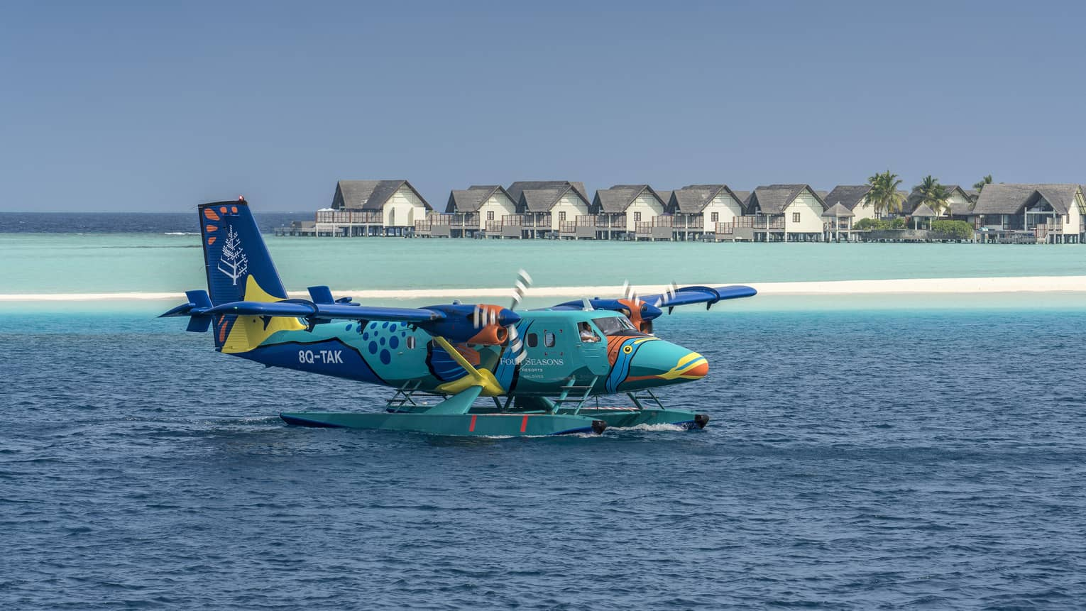 The Four Seasons sea plane landing on calm water in front of beach houses and palm trees