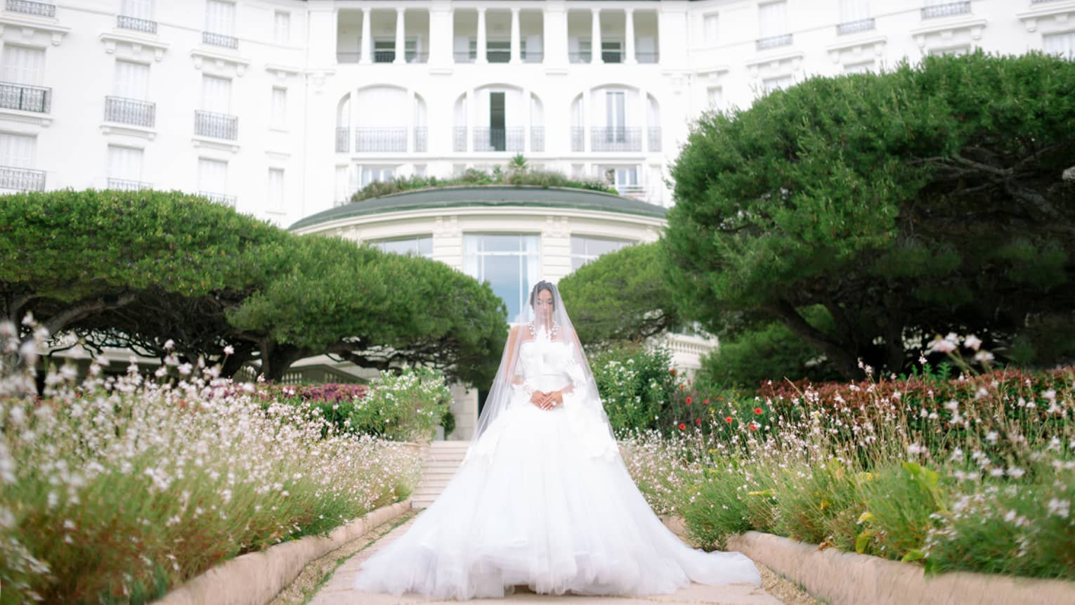 Bride wearing wedding gown and long sheer veil over face stands in garden before Four Seasons Hotel Grand-Hotel du Cap-Ferrat