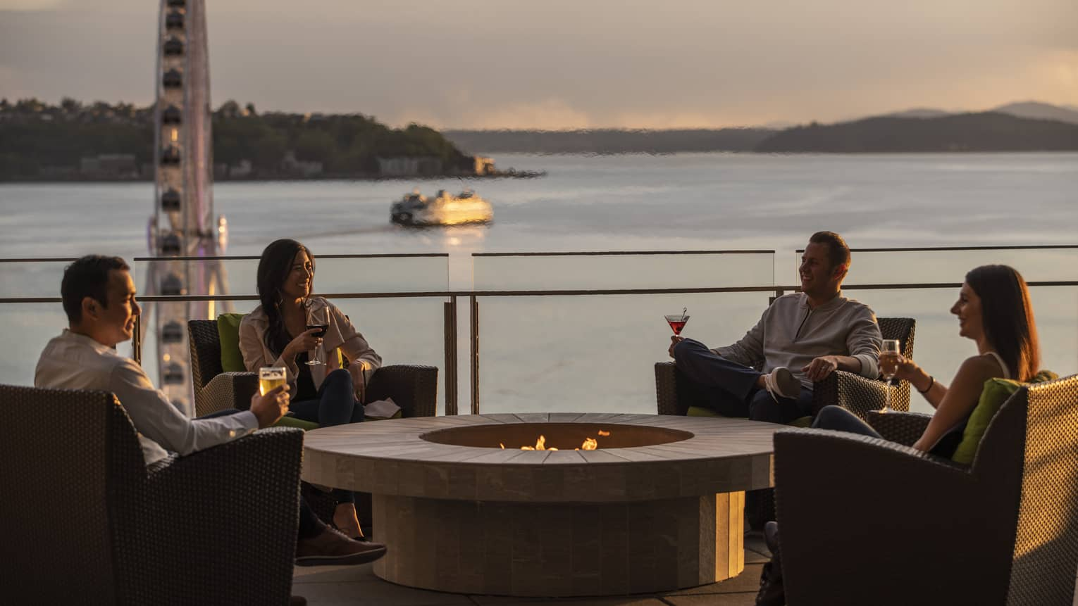 Guests enjoy drinks by the firepit with a view of the Seattle Great Wheel and bay behind them