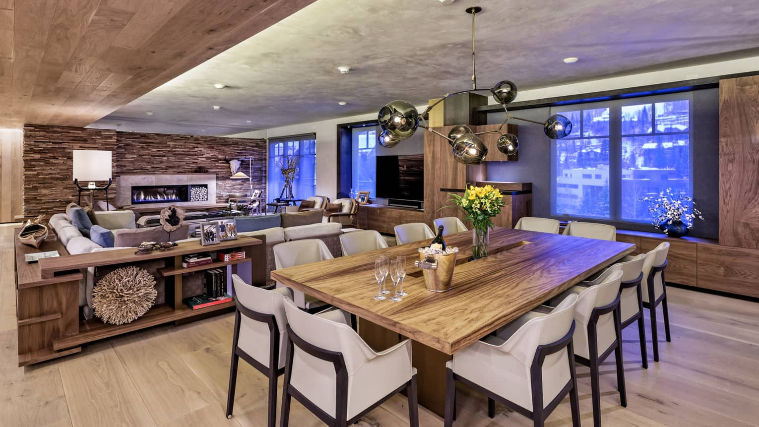 Modern wood farm-style dining table lined with white chairs, Champagne on ice, in front of living room