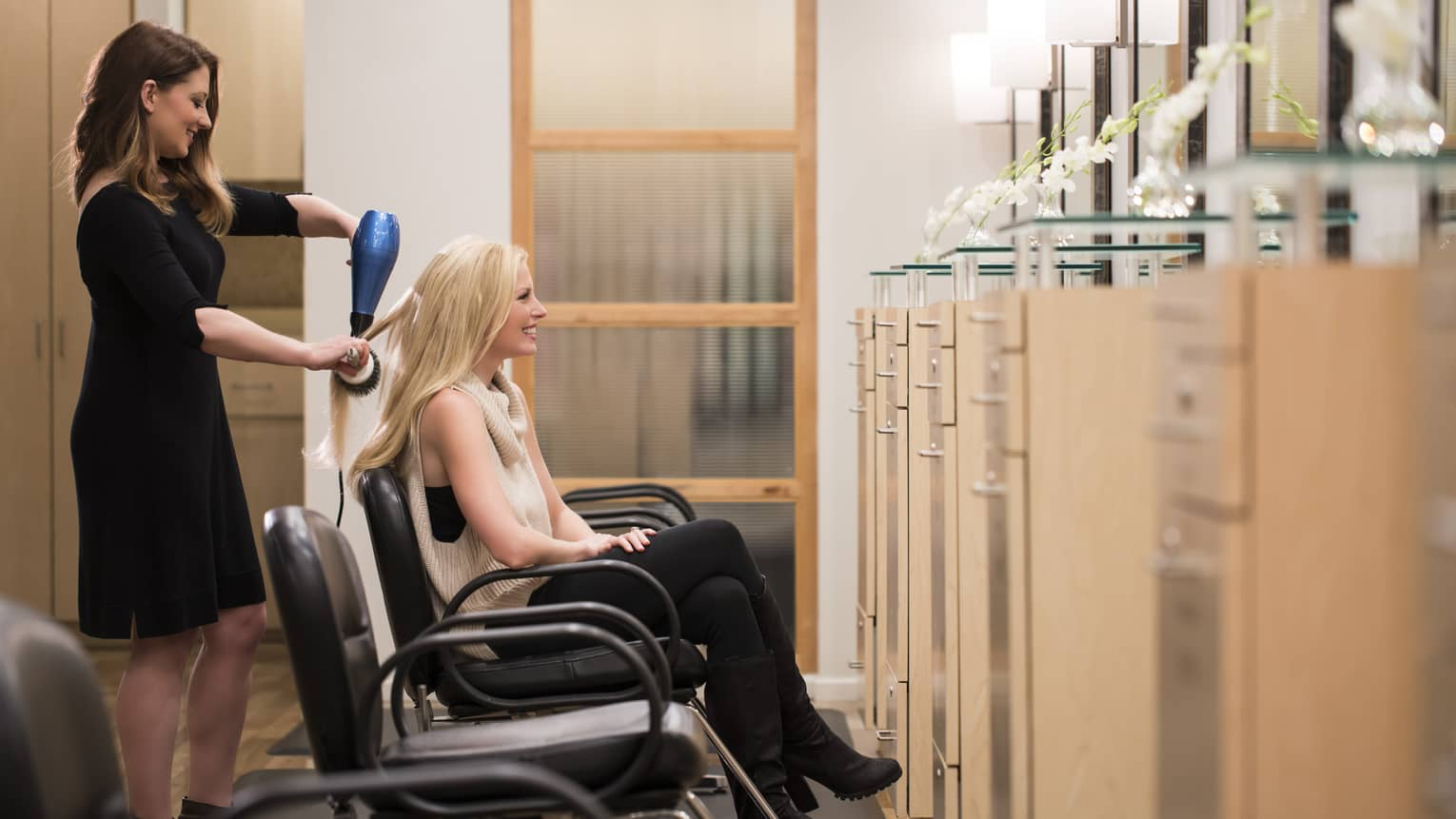 Hairstylist brushes, blow dries woman's long hair as she sits in barber chair in Spa