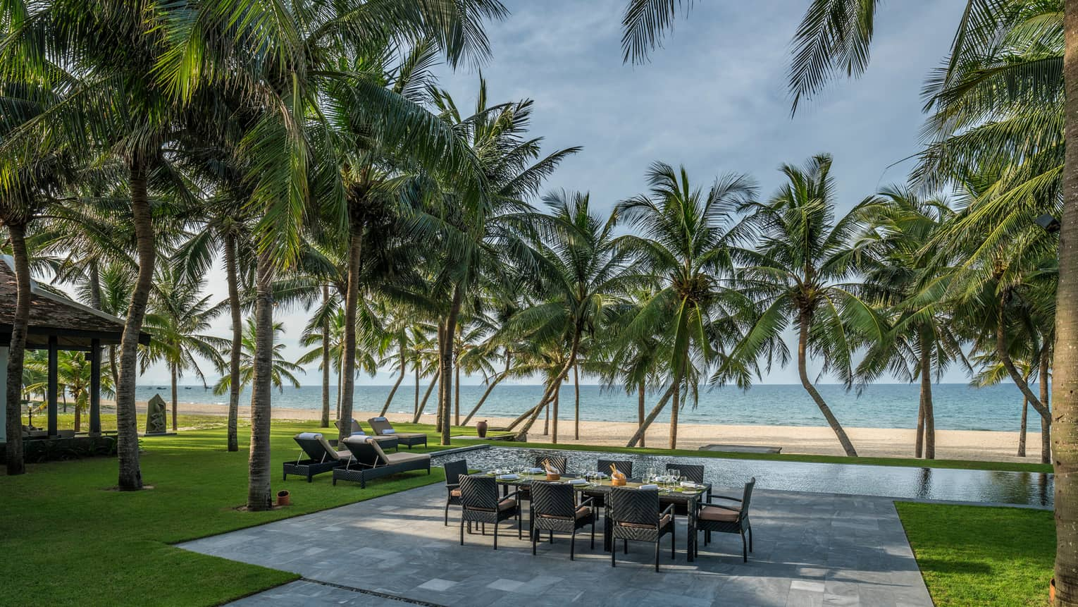 Beachfront Villa large stone patio with private dining table, lounge chairs under palms